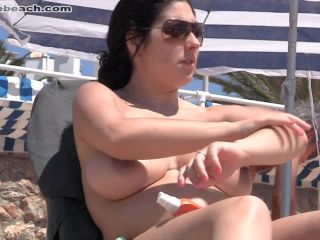 Nude beach, young girl shows big tits