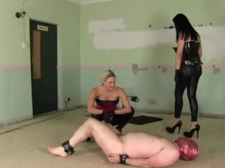 Two strapon Mistresses humiliate a slave while also busting his balls