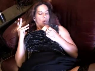 Melissa smokes a cigar on the couch